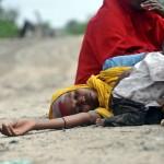 Una mujer espera junto a su hijo para recibir atención médica y alimento en un campamento provisional. | ANTOINE DE RAS (EFE)