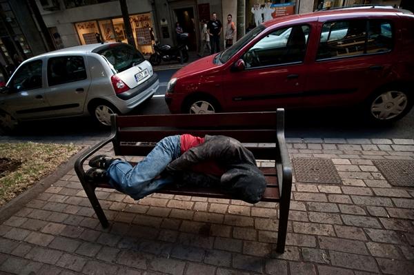 Indigente duerme en un banco