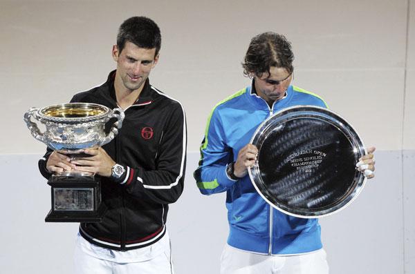 El tenista español Rafa Nadal (d) y el serbio Novak Djokovic (i) posan con sus respectivos trofeos después de la final del Abierto de Australia que disputaron Melbourne, Australia. / EFE