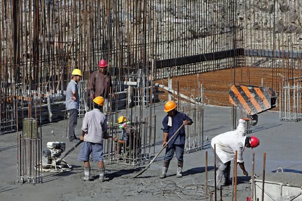 Imagen de archivo de varios trabajadores en la estructura de un edificio en obras. / DA