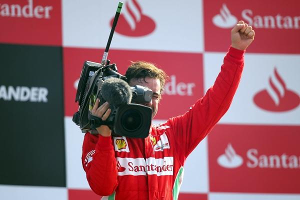 Fernando Alonso, de Ferrari, filma a los espectadores desde el podio