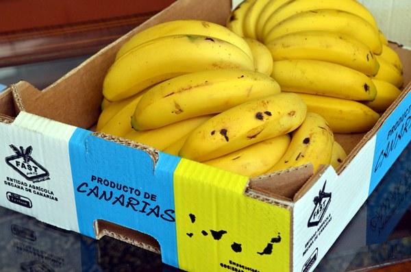 Imagen de una caja con varias manillas de plátano de origen canario. | DA