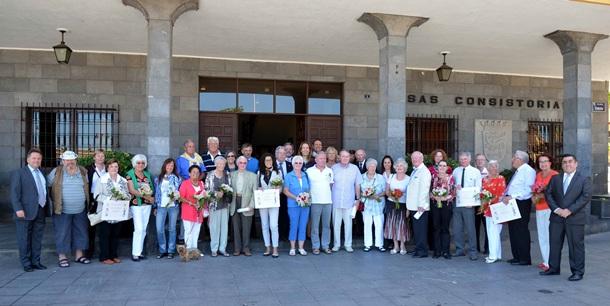 Foto de familia de un grupo de turistas, junto al alcalde y miembros del CIT local. / DA