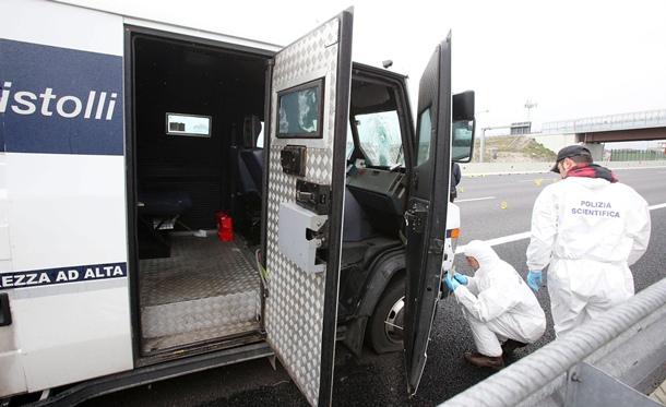 Oficiales de la policía forense inspeccionan un furgón blindado que transportaba 10 millones de euros y que fue asaltado este lunes 8 de abril de 2013, por una decena de hombres armados. | EFE
