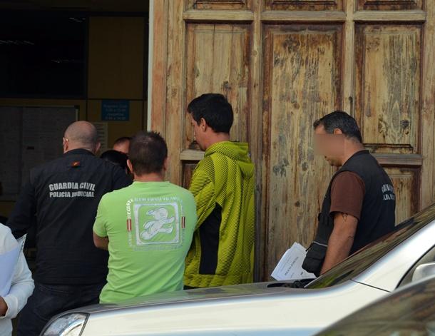 Instante en el que el primero de los dos detenidos entra en el juzgado número 3 de La Orotava, flanqueado por dos agentes policiales / MOISÉS PÉREZ