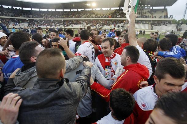 La afición del Hospitalet celebró ayer el campeonato del Grupo III sobre el césped de su estadio junto a los jugadores. / EL 9 ESPORTIU