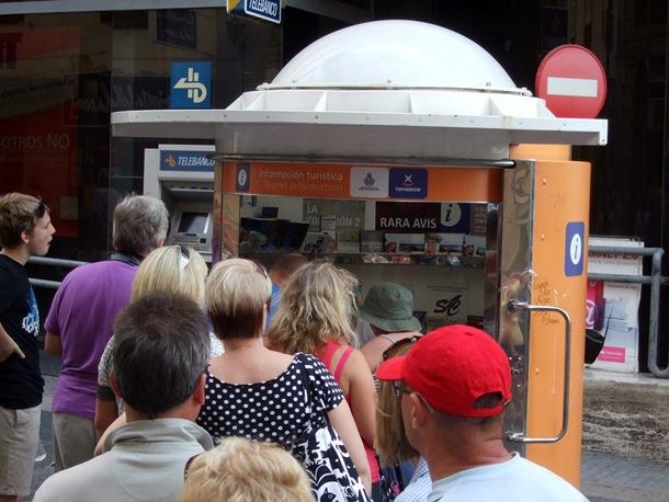 Varios visitantes esperan su turno en una oficina de información turística. | DA
