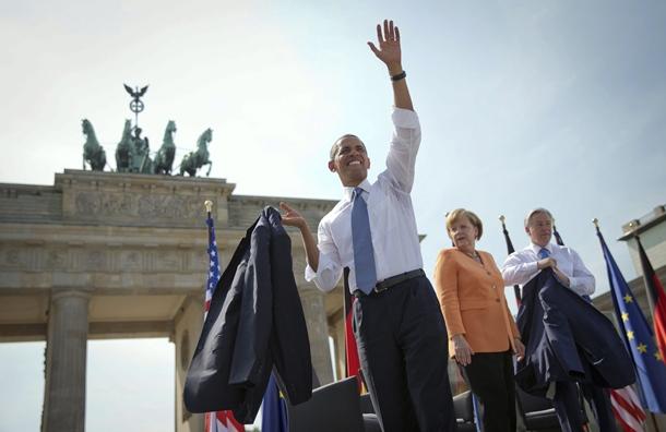 Barack Obama saluda en presencia de la canciller alemana, Angela Merkel, en la Puerta de Brandenburgo