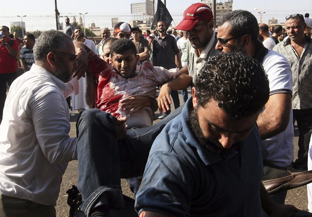Varios hombres trasladan a un herido durante choques entre simpatizantes de los Hermanos Musulmanes del depuesto presidente egipcio Mohamed Mursi y la policía. | EFE