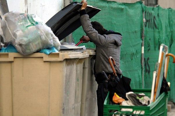 Un sintecho busca alimento en un contenedor de basura. | MOISÉS PÉREZ