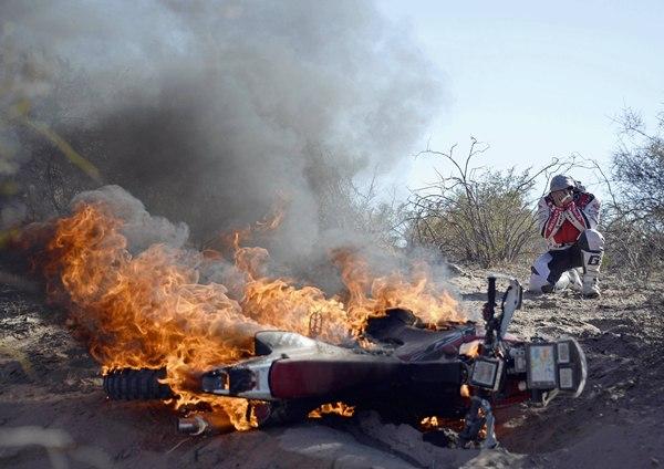 El motorista portugués Paulo Goncalves ante su moto ardiendo durante el Dakar. | REUTERS/Stringer