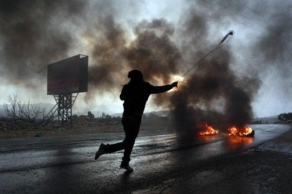 Un palestino lanza una piedra con una honda a las tropas israelíes como protesta por el asentamiento judía de Ofra. |  REUTERS
