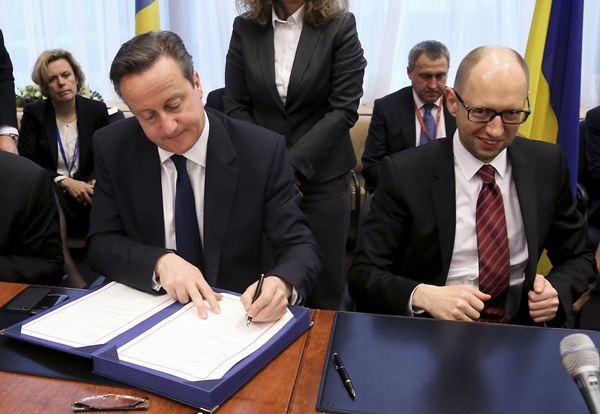 El ministro británico y el ucraniano durante la firma del acuerdo que pone a Ucrania más cerca de Europa. / REUTERS