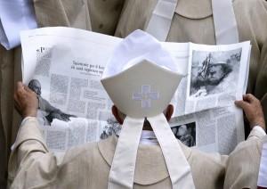 Un obispo mira un periódico local en el que se glosan las figuras de Juan XXIII y Juan Pablo II | REUTERS