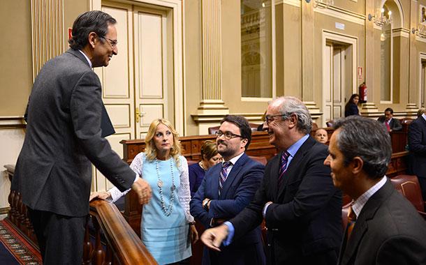 """El presidente del Parlamento canario, Antonio Castro (CC), habla con diputados del PP: """"¿Qué apostamos?"""". / SERGIO MÉNDEZ"""