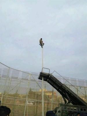 Un hombre encaramado en una farola de la valla de Melilla.   REUTERS