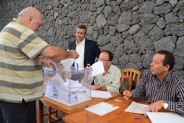 El concejal Dámaso Arteaga mira a un votante durante la consulta de los taxistas en el Pancho Camurria.   S. MÉNDEZ
