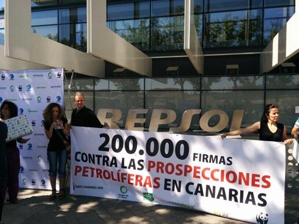 Representantes de los ecologistas, ante la sede de Repsol en Madrid, para entregar las firmas. / DA