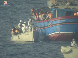 Migrants climb aboard a lifeboat during a rescue operation by Italian navy ship Grecale off the coast of Sicily