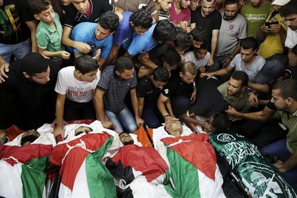 Cadáveres de palestinos fallecidos en los bombardeos, envueltos en la bandera de Palestina. / REUTERS