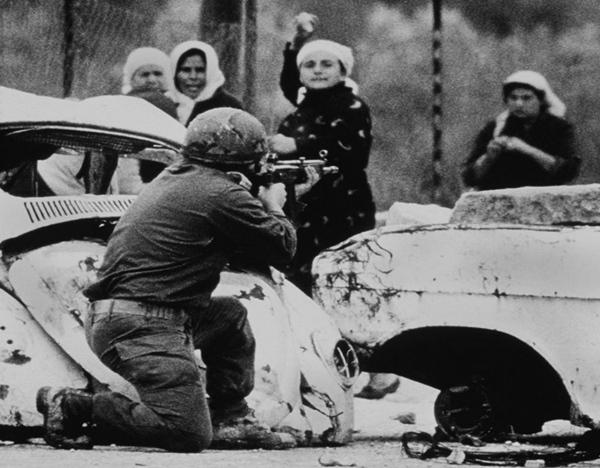 Palestinos tirando piedras a un militar israelí durante la Intifada. | REUTERS