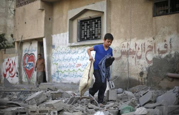 Un niño palestino desaloja su casa bombardeada. | REUTERS