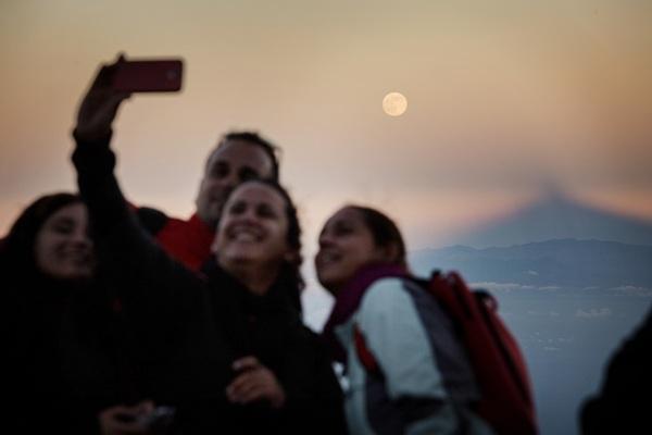 Un grupo de jóvenes, en el pico, con la superluna y la sombra del Teide al fondo. / A. G.