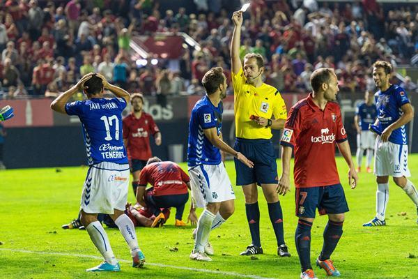 El árbitro le muestra la amarilla a Javi Moyano. | REUTERS