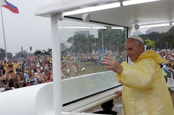 El papa Francisco saluda a los fieles durante su recorrido por las calles de Manila. / REUTERS