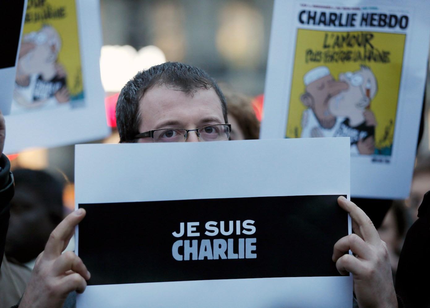 Parte de los asistentes han mostrado pancartas de apoyo a la revista, algunas de ellas con imágenes de caricaturas de Mahoma. Otros de los manifestantes han alzado lápices y bolígrafos como gesto de apoyo a la libertad de expresión./ REUTERS