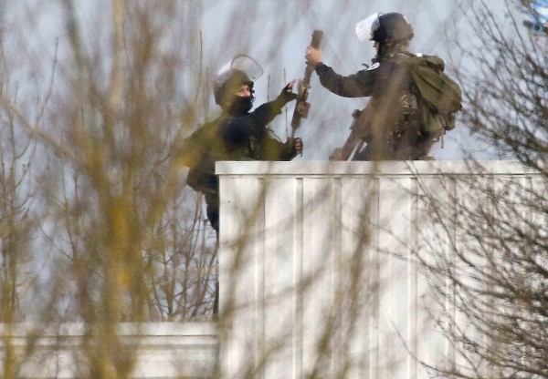 French special forces handle arms as they take position on a rooftop of the complex at the scene of a hostage taking at an industrial zone in Dammartin-en-Goele
