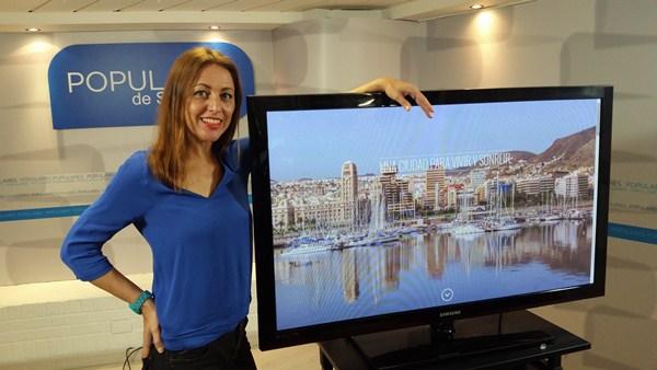 Cristina Tavío, junto a la portada de la página web en la que expone su programa electoral. / DA
