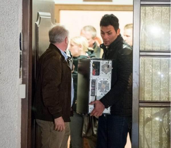 Un agente se lleva el ordenador del copiloto durante el registro domiciliario. | REUTERS