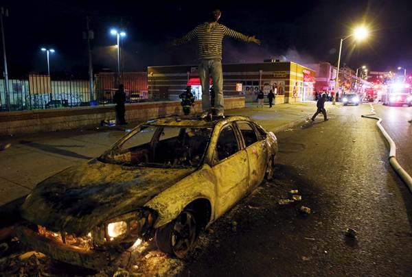 Un hombre subido a un coche quemado durante los disturbios de anoche en Baltimore.   REUTERS