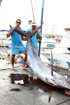 El marlin azul y sus captores en Puerto Colón ayer tarde. / Gerard Zenou