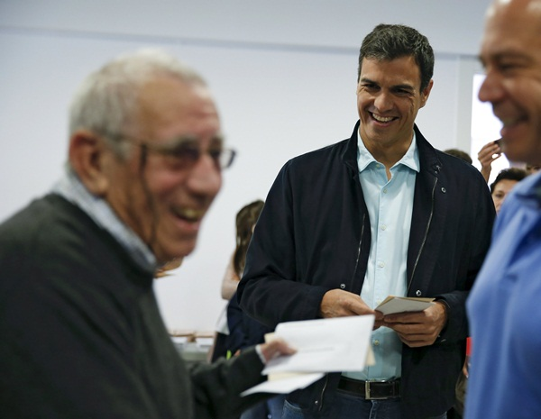 Spain's Socialist Party PSOE leader Sanchez smiles while talking to a voter at a polling station during regional and municipal elections in Pozuelo de Alarcon