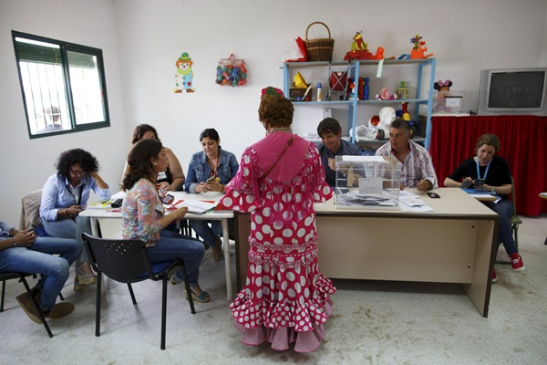 A woman wearing traditional 'Rociera' outfit votes at a polling station during regional and municipal elections in El Rocio village, southern Spain