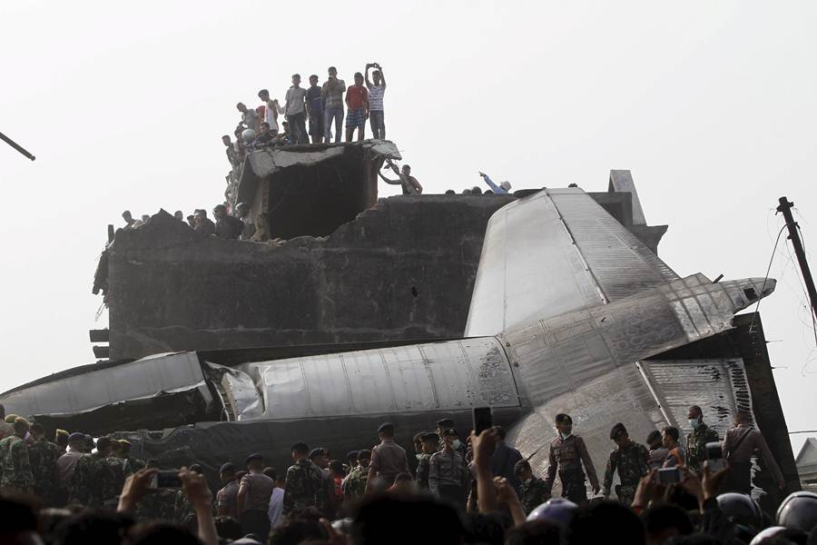 Security forces and residents examine the wreckage of an Indonesian military C-130 Hercules transport plane after it crashed into a residential area in the North Sumatra city of Medan, Indonesia, June 30, 2015. At least 49 people were reported dead after a military transport plane crashed into a residential area shortly after take-off in northern Indonesia on Tuesday, but the toll looked set to rise after it emerged that more than 100 people had been on board. REUTERS/Roni Bintang TPX IMAGES OF THE DAY