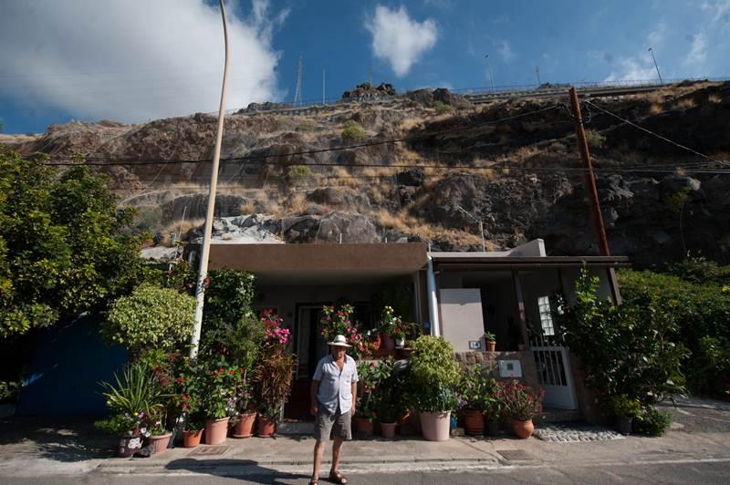 Uno de los vecinos, por fuera de su casa en Bajo la Cuesta, con el acantilado y la TF-1 a sus espaldas. / FRAN PALLERO