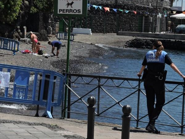 Una policía local observa la playa cerrada al baño de manera provisional.  / NORCHI
