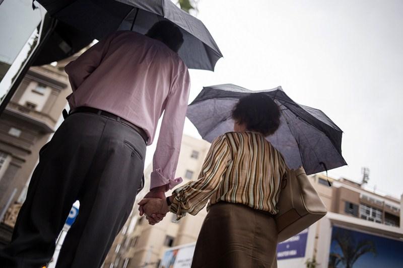 Los paraguas volvieron a hacer acto de presencia ayer. A la derecha, los rayos registrados por la Aemet. / A.G.