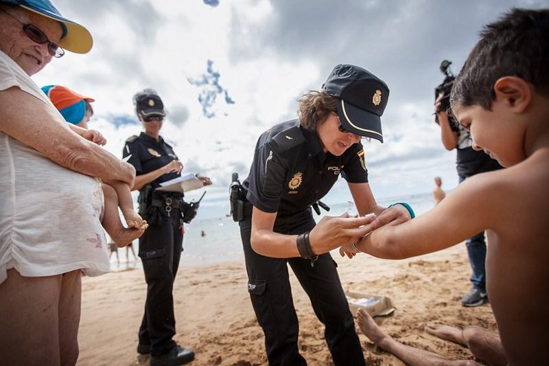 Agentes de la Policía Nacional colocaron ayer pulseras a niños en la playa de Las Teresitas. / ANDRÉS GUTIÉRREZ