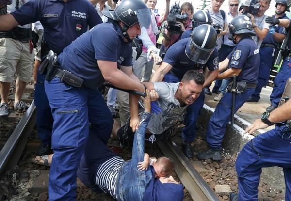 La Policía húngara interviene para retirar de las vías del tren a los miembros de una familia de refugiados, ayer, en la ciudad de Bickse.   REUTERS/Laszlo Balogh