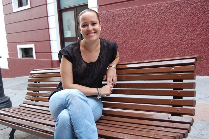 La fisioterapeuta oncológica Raquel Pérez García, sentada frente al Ayuntamiento de la villa de Arafo. / DA