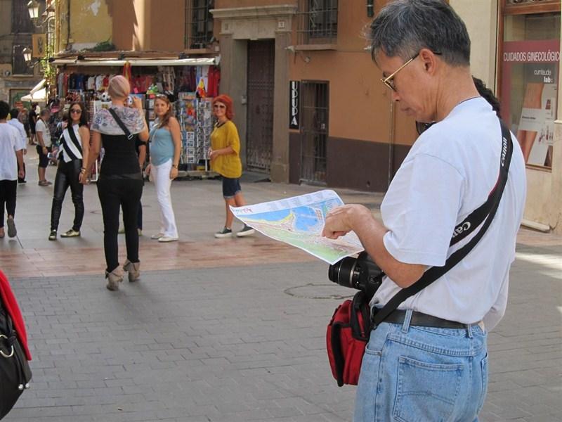 Imagen de archivo de un turista asiático mirando un mapa. / EP