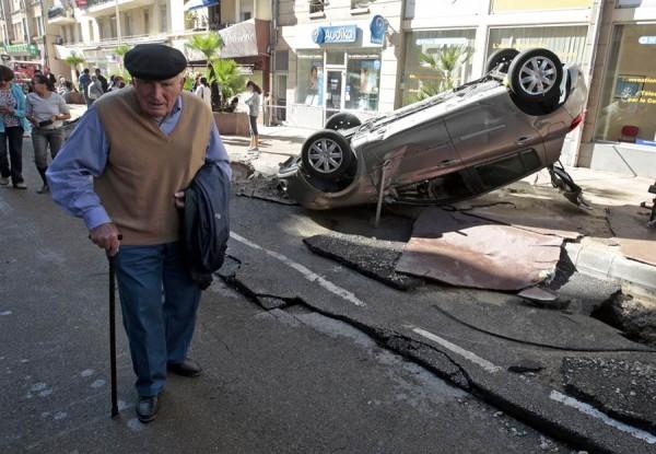 Un señor pasea entre los destrozos que han dejado las inundaciones.   REUTERS