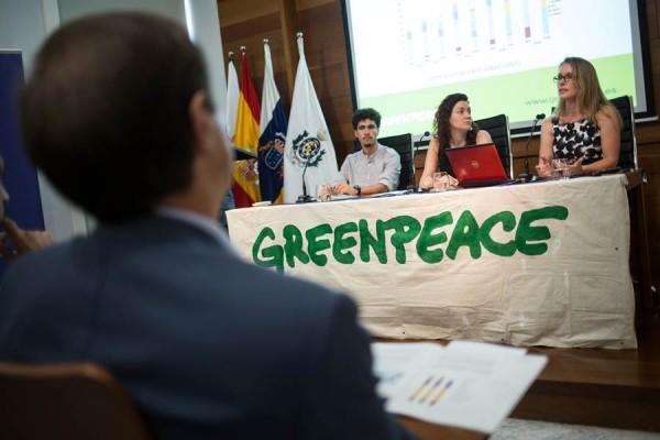 Los activistas de Greenpeace y, de espaldas, un representante de Endesa, en el acto como público. | A. GUTIÉRREZ