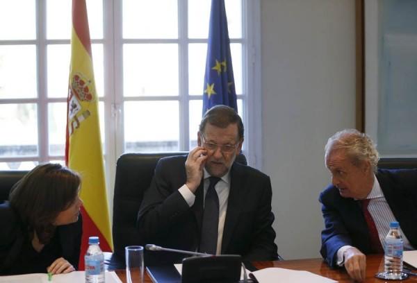 Mariano Rajoy habla con el ministro de Defensa Pedro Morenes  y la vicepresidenta Soraya Saenz de Santamaria al comienzo de la reunión del Consejo de Seguridad Nacional. | REUTERS