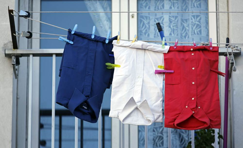 Blue, white and red shirts, the colours of the French national flag, hang from a balcony in Marseille