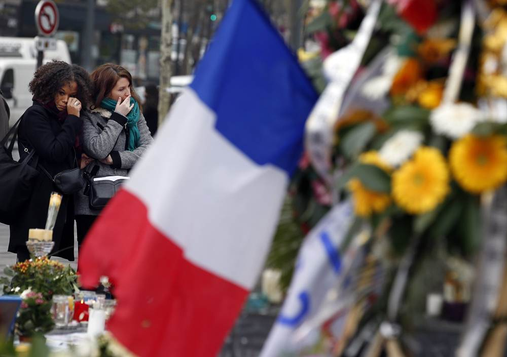 Two women cry as they pay tribute to the victims of Paris attacks at the Place de la Republique in Paris
